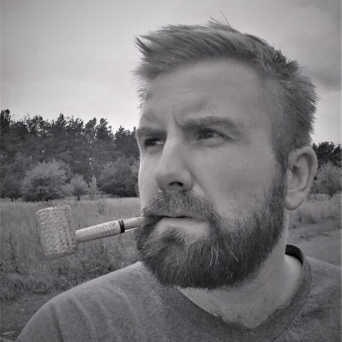 Ja czyli Kuba Dębski, myślący, z fajką z zębach, na tle lasu.